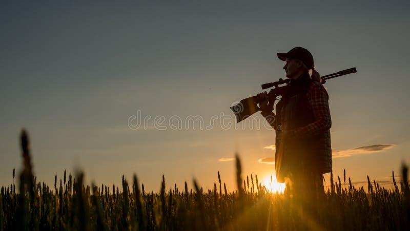 妇女猎人剪影  它在有枪的一个美丽如画的地方站立在日落 射击和寻找概念的体育 免版税库存照片