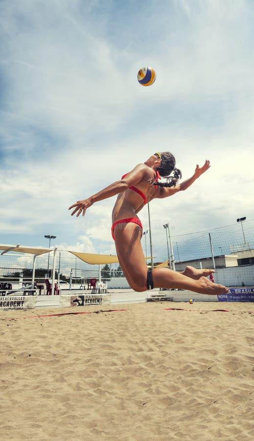 妇女球员jumoing的沙滩排球击中球 峰值 库存照片