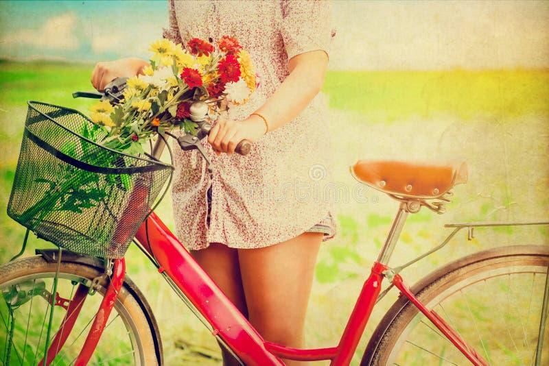 妇女生活方式在有五颜六色的花的春天在红色自行车篮子  免版税图库摄影