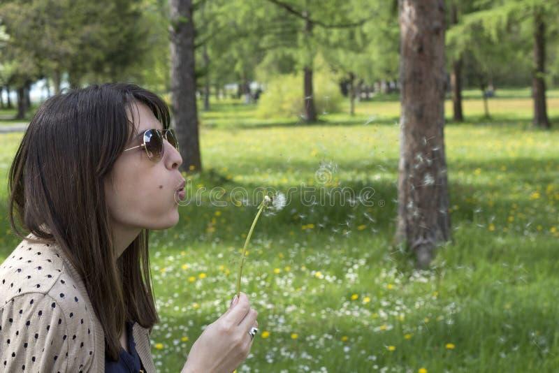 妇女用一个蒲公英在公园 免版税图库摄影