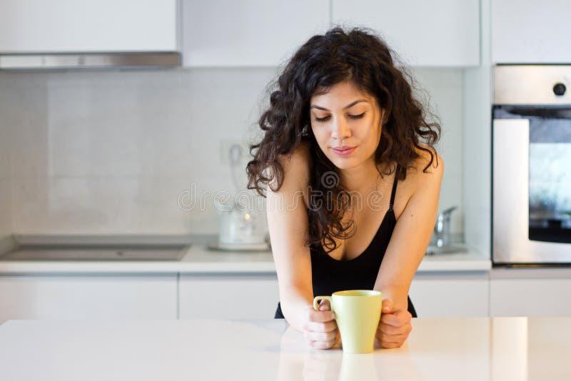 妇女用咖啡或茶在厨房里 免版税库存照片