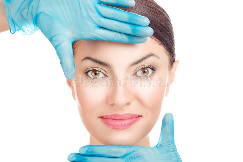 妇女用在手套的医生手在面孔附近 免版税库存照片
