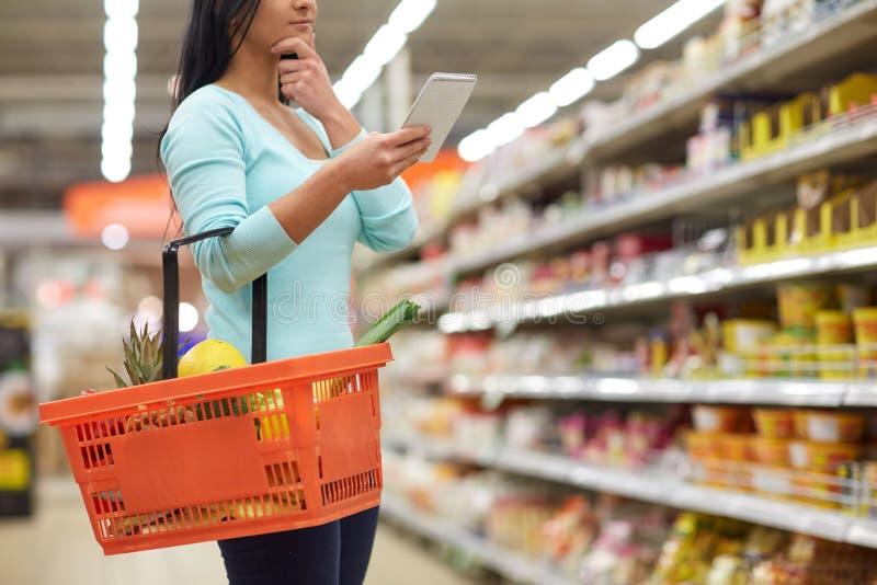 妇女用在手提篮的食物在超级市场 免版税库存图片