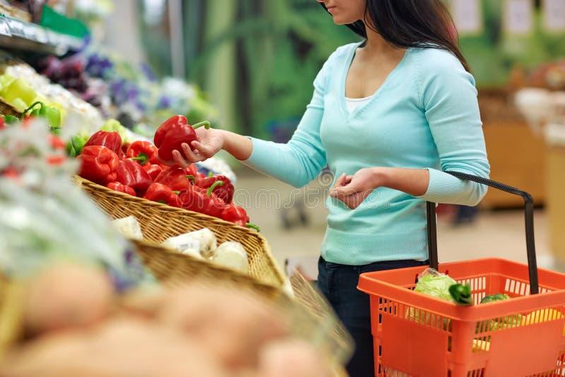 妇女用在杂货店的篮子买的胡椒 库存图片
