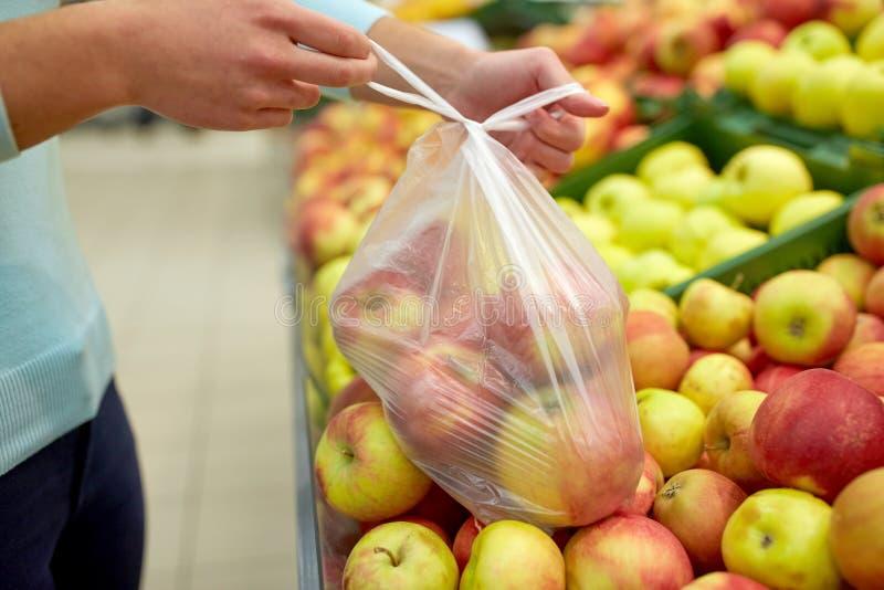 妇女用在杂货店的袋子买的苹果 免版税库存照片
