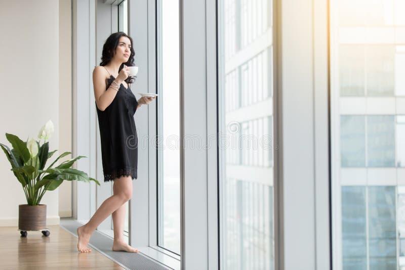 妇女用在窗口附近的咖啡 免版税库存照片