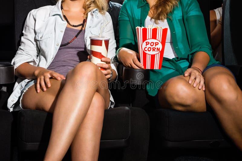 妇女用坐在剧院的玉米花和苏打 免版税库存图片