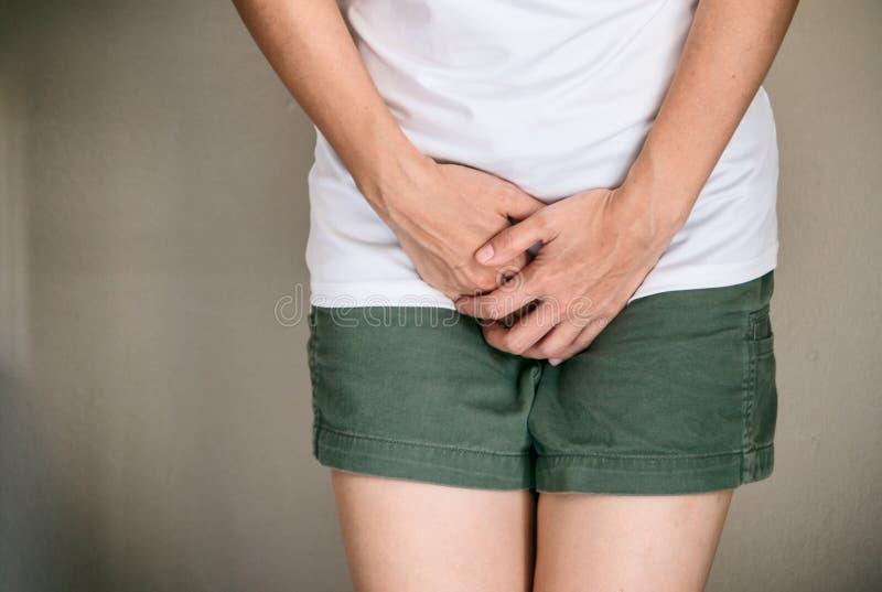 妇女用拿着她要撒尿的她的裤裆,泌尿p的手 库存照片