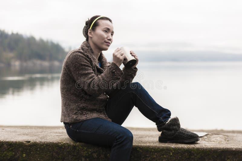 妇女用由湖的咖啡 免版税库存图片
