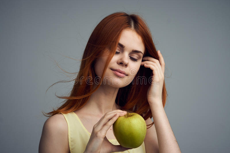 妇女用苹果,饮食,营养,妇女看在灰色背景的一个绿色苹果 免版税库存图片