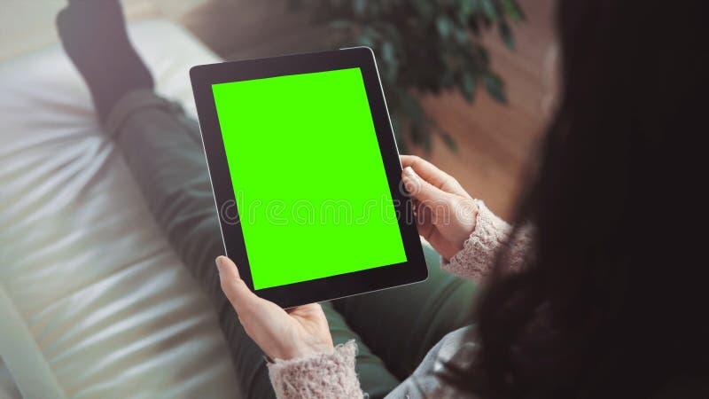 妇女用途片剂个人计算机坐沙发 库存照片
