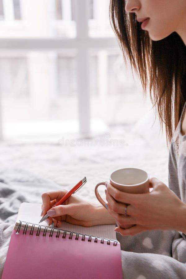 妇女用采取笔记的饮料 免版税库存图片