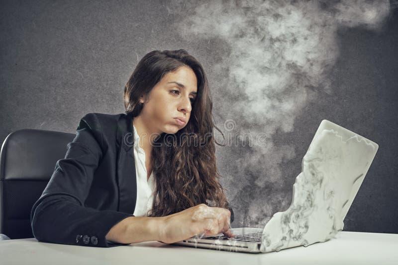 妇女由与膝上型计算机熔化的劳累过度强调说 库存照片