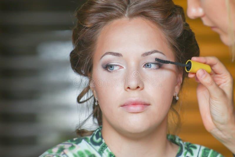 妇女由染睫毛油的刷子做睫毛和眼睛的新娘构成 库存照片
