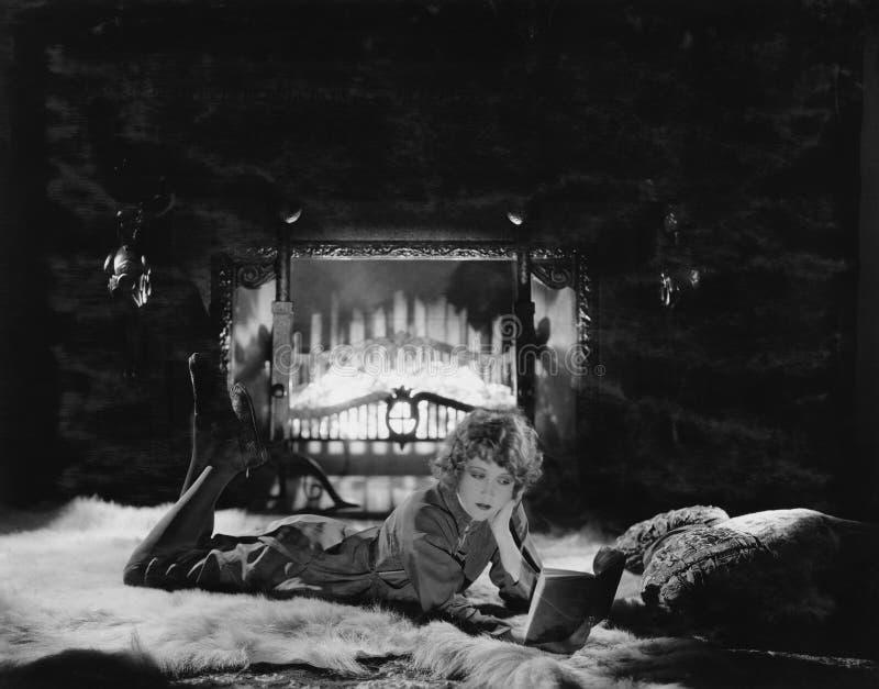 妇女由火的阅读书(所有人被描述不更长生存,并且庄园不存在 供应商保单那里w 免版税图库摄影