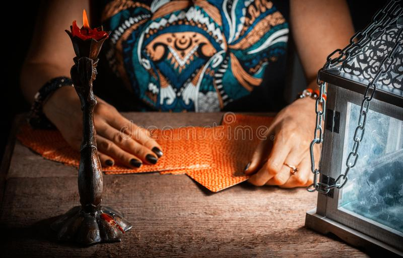 妇女由灯笼和一个蜡烛的光计划占卜用的纸牌 免版税库存照片