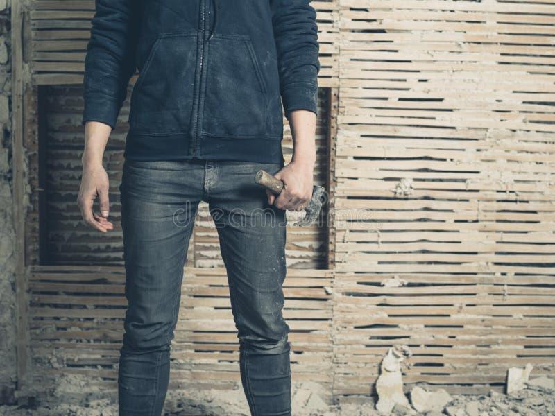 妇女由篱笆条和涂抹墙壁的wih锤子 库存图片