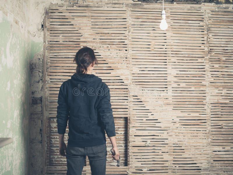 妇女由篱笆条和涂抹墙壁的wih锤子 库存照片