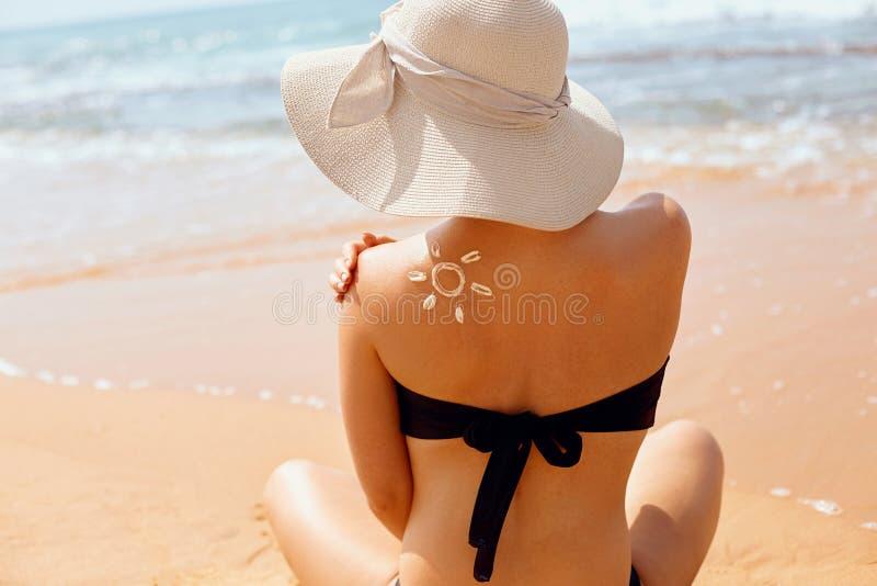 妇女申请在被晒黑的肩膀的防晒霜保护 秀丽skincare老化身体关心 库存照片