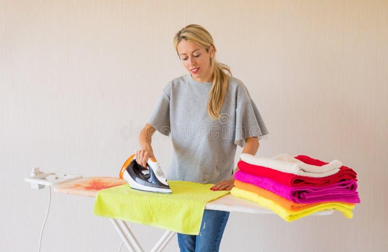 妇女电烙的衣裳在家 免版税库存照片