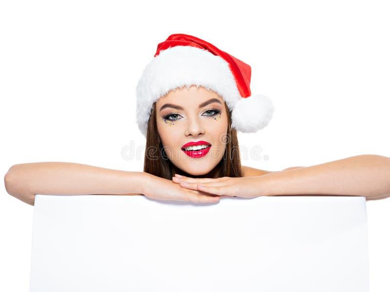 妇女画象一个圣诞老人帽子的有横幅的 与在白色-隔绝的明亮的创造性的构成的美丽的微笑的妇女的面孔 库存照片