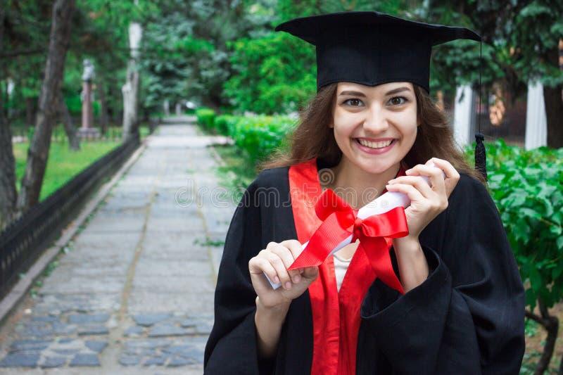 妇女画象在她的毕业典礼举行日 大学 教育、毕业和人概念 免版税库存图片
