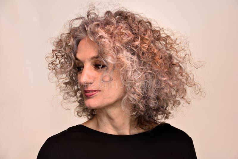 妇女画象有美妙的卷发的 免版税库存照片