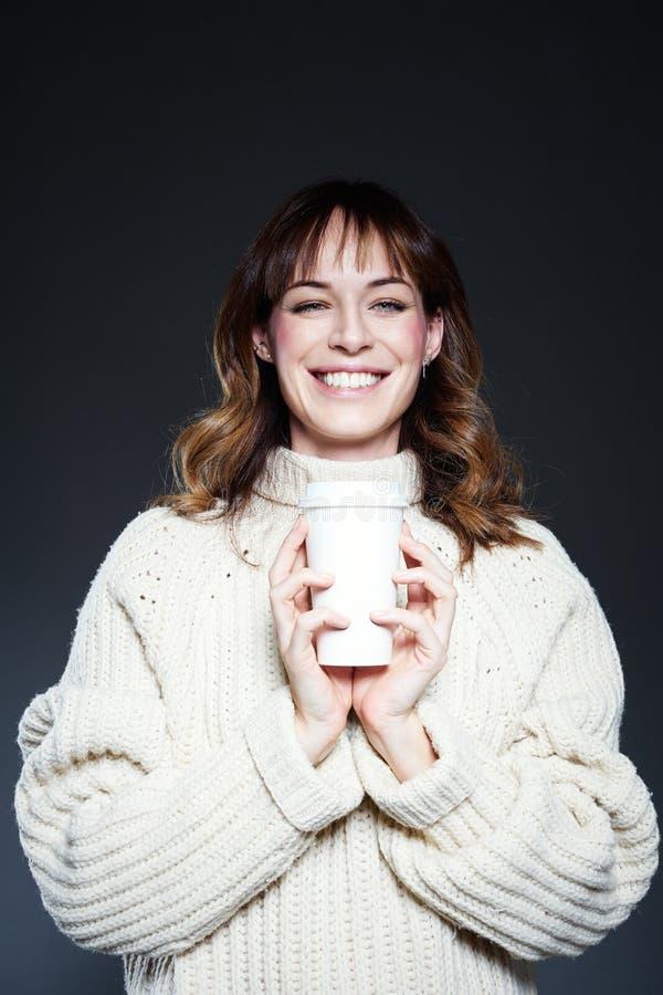 妇女画象有长发的有外带的一次性咖啡的在手上,佩带的白色冬天毛线衣,深灰backgrou 库存照片