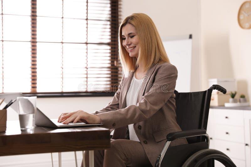 妇女画象轮椅工作的与膝上型计算机在桌上 免版税库存照片