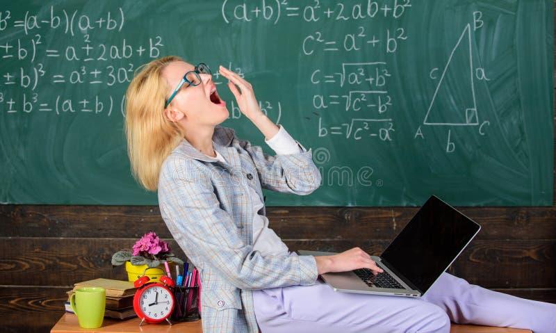 妇女疲倦了老师工作膝上型计算机教室黑板背景 老师的工作环境 工作环境 免版税库存照片