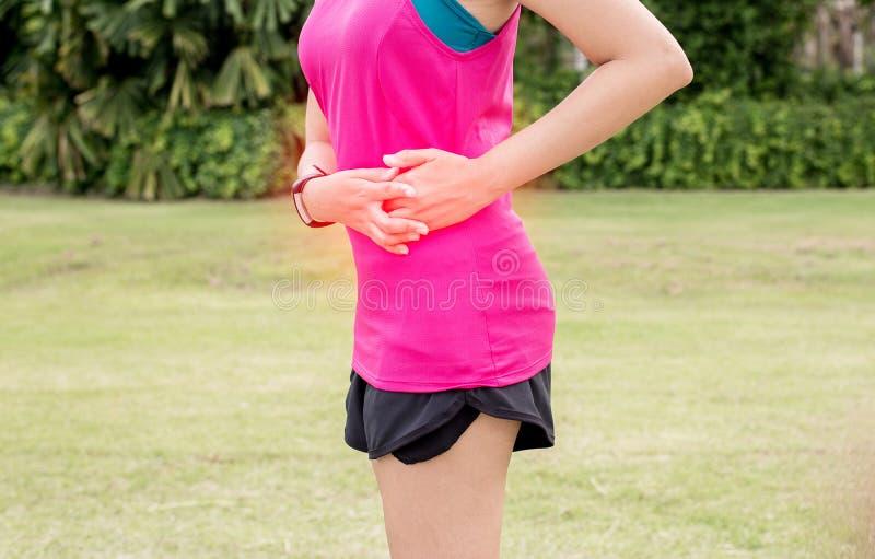妇女痛苦有胃痛,在体育锻炼赛跑以后的女性赛跑者边抽疯 免版税库存图片