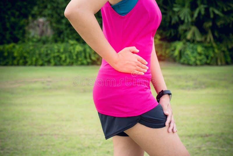 妇女痛苦有胃痛,在体育锻炼赛跑以后的女性赛跑者边抽疯 免版税库存照片