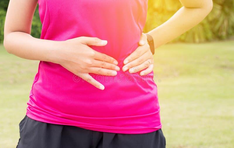 妇女痛苦有胃痛,女性赛跑者边抽疯,当体育锻炼赛跑时 库存图片
