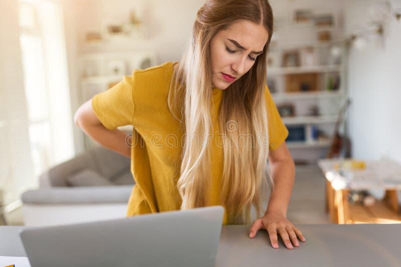 妇女痛苦腰疼,当使用膝上型计算机时 库存图片