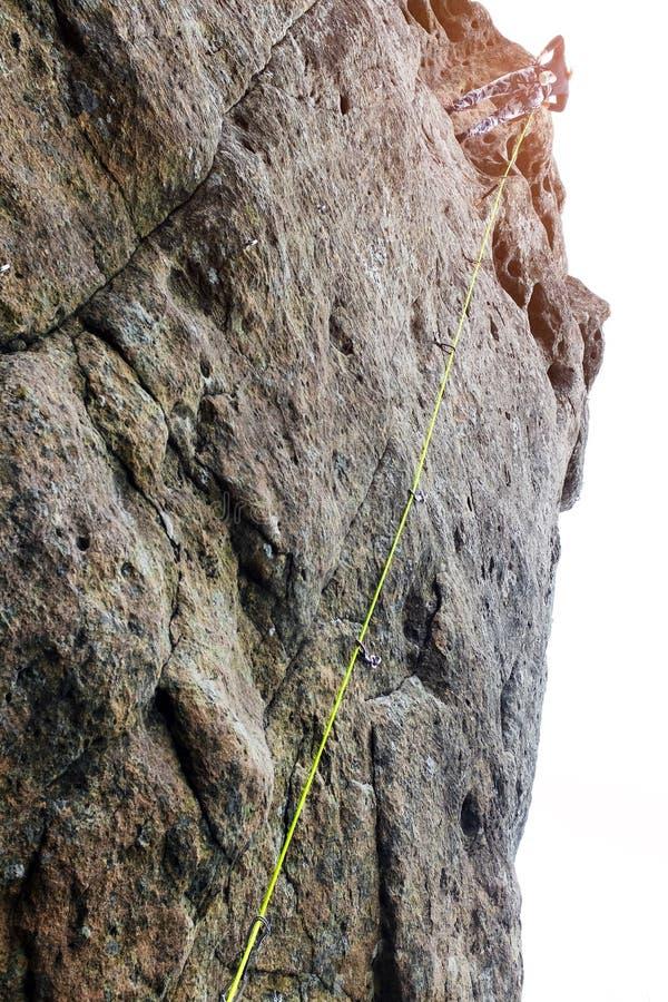 妇女登山家,年轻人攀登在岩石的登山家一条困难的路线 登山人攀登岩石墙壁 安全绳索 免版税库存照片