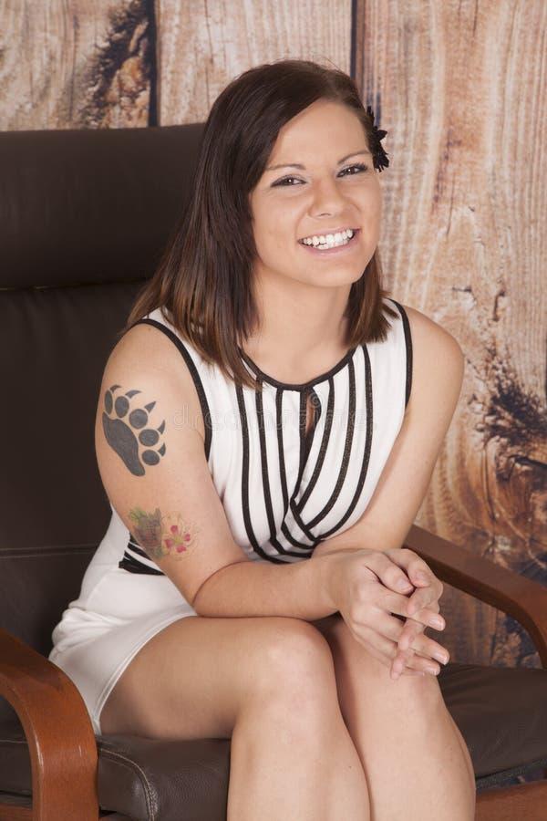 妇女白色礼服坐爪纹身花刺微笑 免版税库存图片