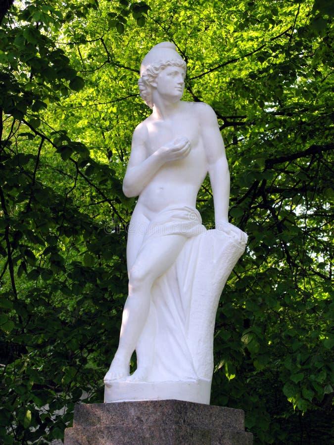 妇女的一个典雅的雕象由膏药制成 站立在树中绿色丛林的一个垫座  免版税库存照片