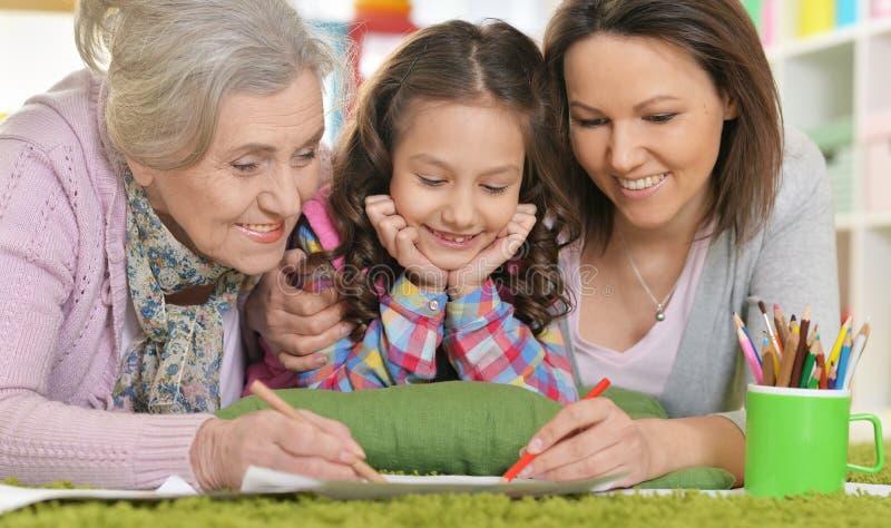 妇女的三世代从说谎在地板和博士上的一个家庭的 库存照片
