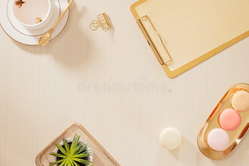 妇女的与剪贴板,蛋白杏仁饼干,笔,在淡色背景的咖啡杯的家庭办公室工作区 平的位置,顶视图生活方式 免版税图库摄影