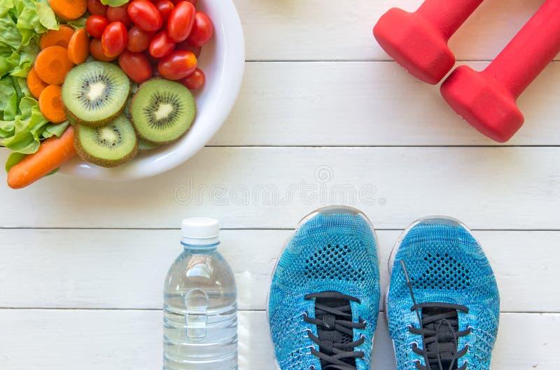 妇女的健康生活方式节食用运动器材、运动鞋,测量的磁带,菜新鲜和瓶在木的水 免版税库存图片