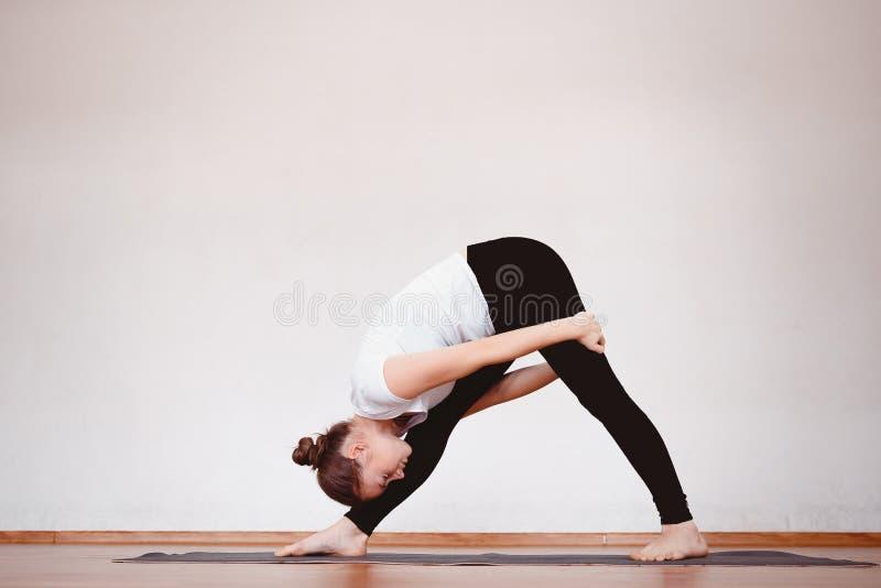 妇女的关闭在训练大厅或家里时思考,当实践瑜伽 免版税库存照片