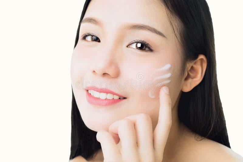 妇女的关闭是微笑的皮肤秀丽和健康并且应用在面孔的白色奶油,为了温泉产品并且组成 图库摄影