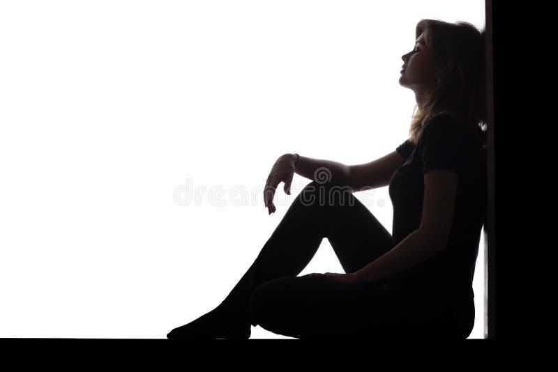 妇女的剪影坐在一个角落的地板在白色被隔绝的背景,一个哀伤的女孩考虑问题的,概念 免版税库存图片