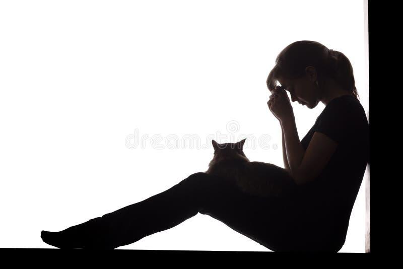 妇女的剪影坐在白色被隔绝的背景的地板与在她的胳膊的一只猫,一哀伤女孩祈祷 免版税图库摄影