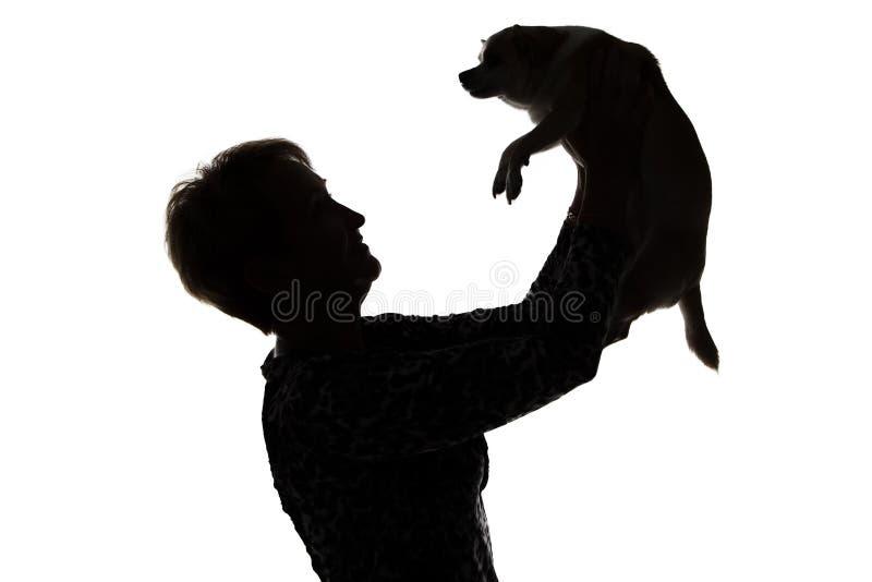 妇女的剪影的照片与狗的 免版税库存照片