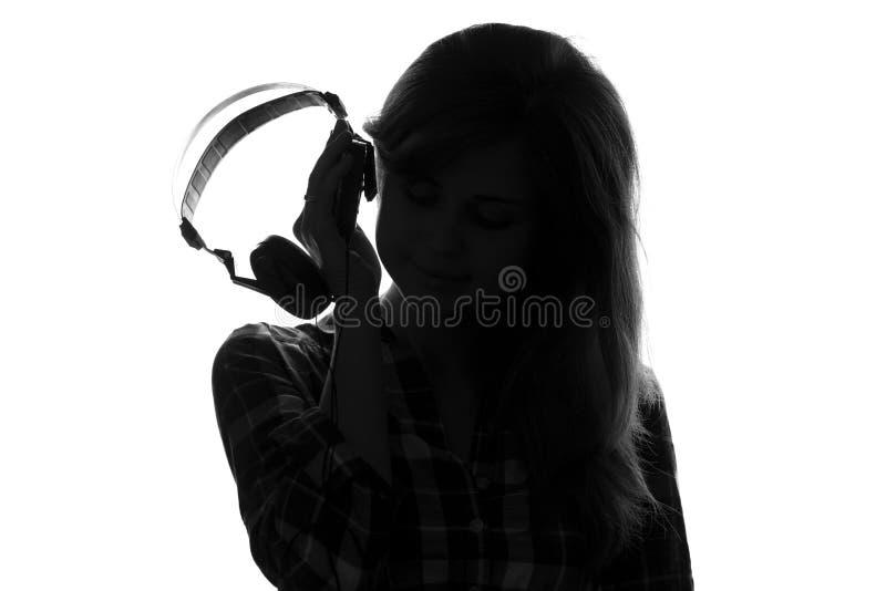 妇女的剪影被投入对他的听到音乐的耳朵耳机 免版税库存图片