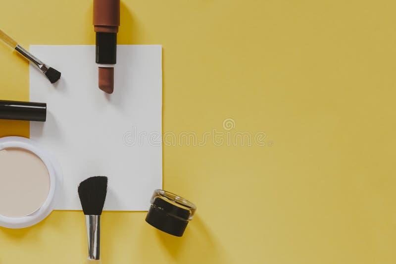 妇女的化妆用品和辅助部件和白皮书在黄色背景 美容品 o r 免版税库存图片