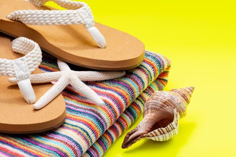妇女的原因自然颜色海滩触发器和五颜六色的镶边用白指海星和贝壳装饰的海滩毛巾 免版税库存照片