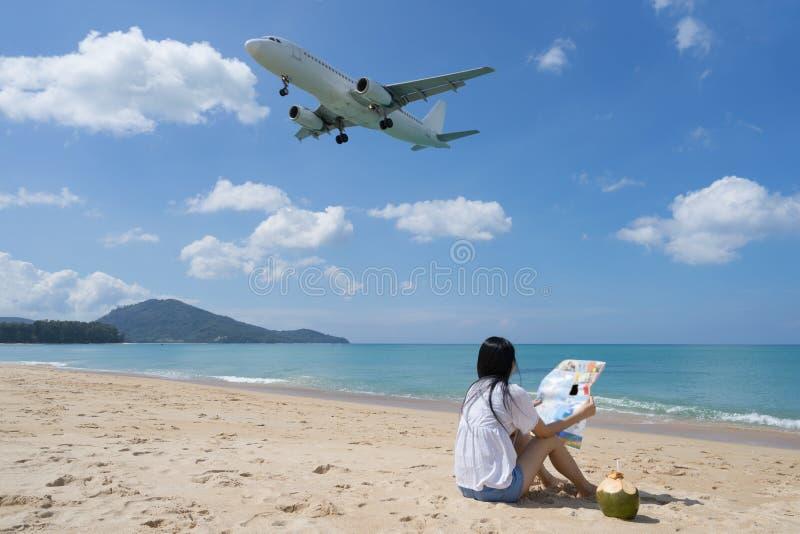 妇女的后部坐海滩和看的地图, Backgrou 免版税库存照片