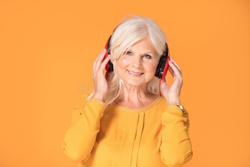 妇女的听的音乐前辈 免版税库存图片